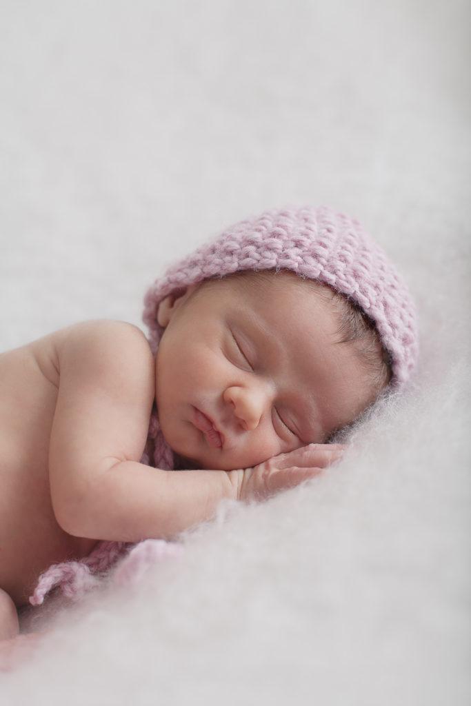 bébé qui dort avec un bonnet rose